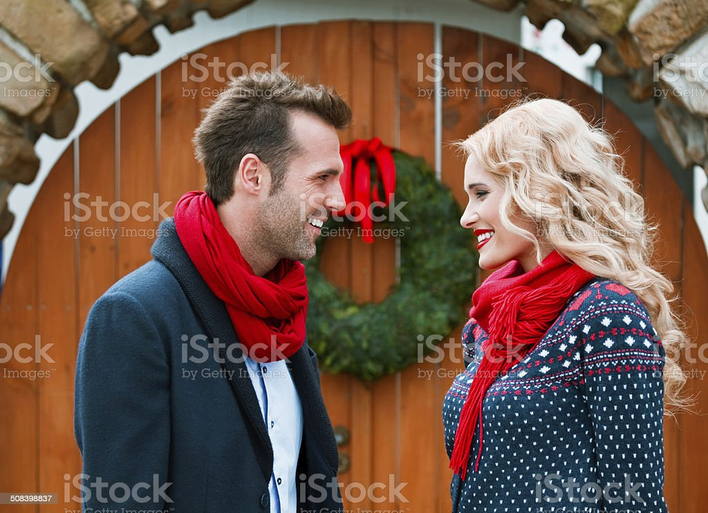 Couple on winter holidays Outdoor portrait of beautiful couple wearing warm clothing looking at each other with door decorated with christmas wreath in the background. Adult Stock Photo
