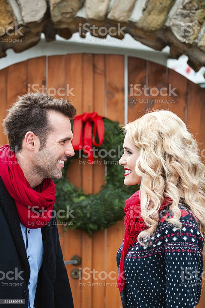 Couple on winter holidays Outdoor portrait of beautiful couple wearing warm clothes looking at each other with door decorated with christmas wreath in the background. Adult Stock Photo