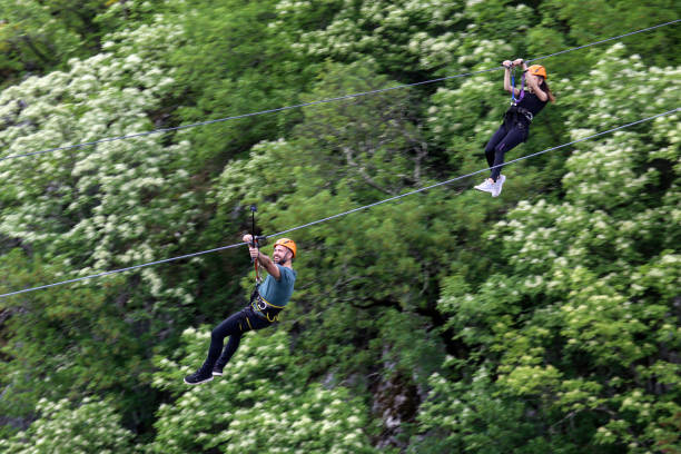 Couple on zip line Young couple having fun on zip line. Both Caucasian people. zip line stock pictures, royalty-free photos & images