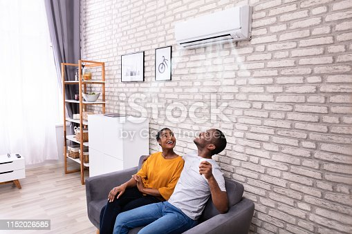 istock Couple Operating Air Conditioner At Home 1152026585
