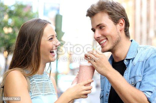 930265372 istock photo Couple or friends sharing a milkshake 535487900