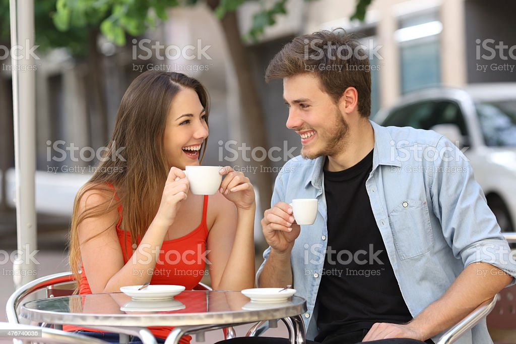 Couple or friends talking and drinking in a restaurant stock photo