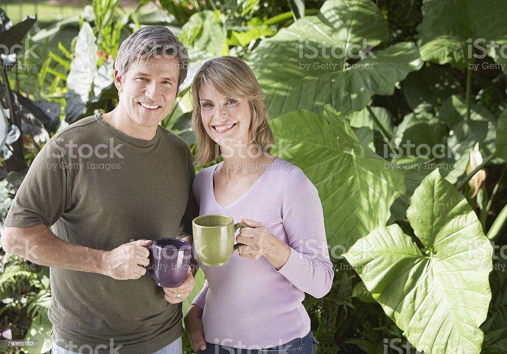 Couple outdoors by trees holding mugs royalty-free stock photo