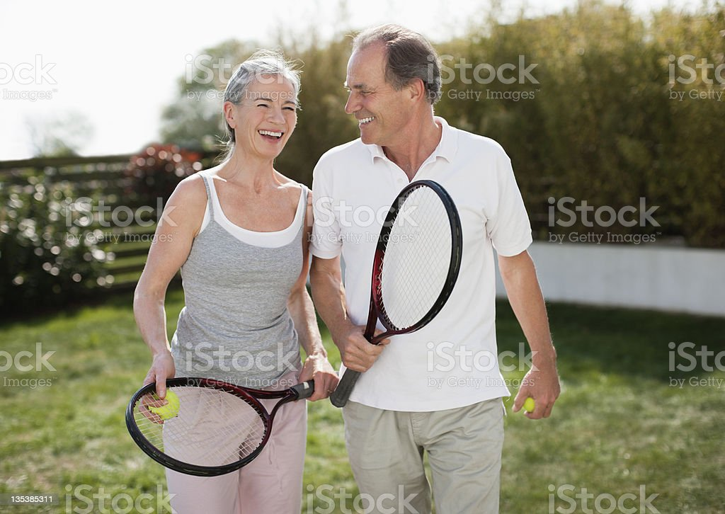 Couple outdoors holding tennis rackets stock photo