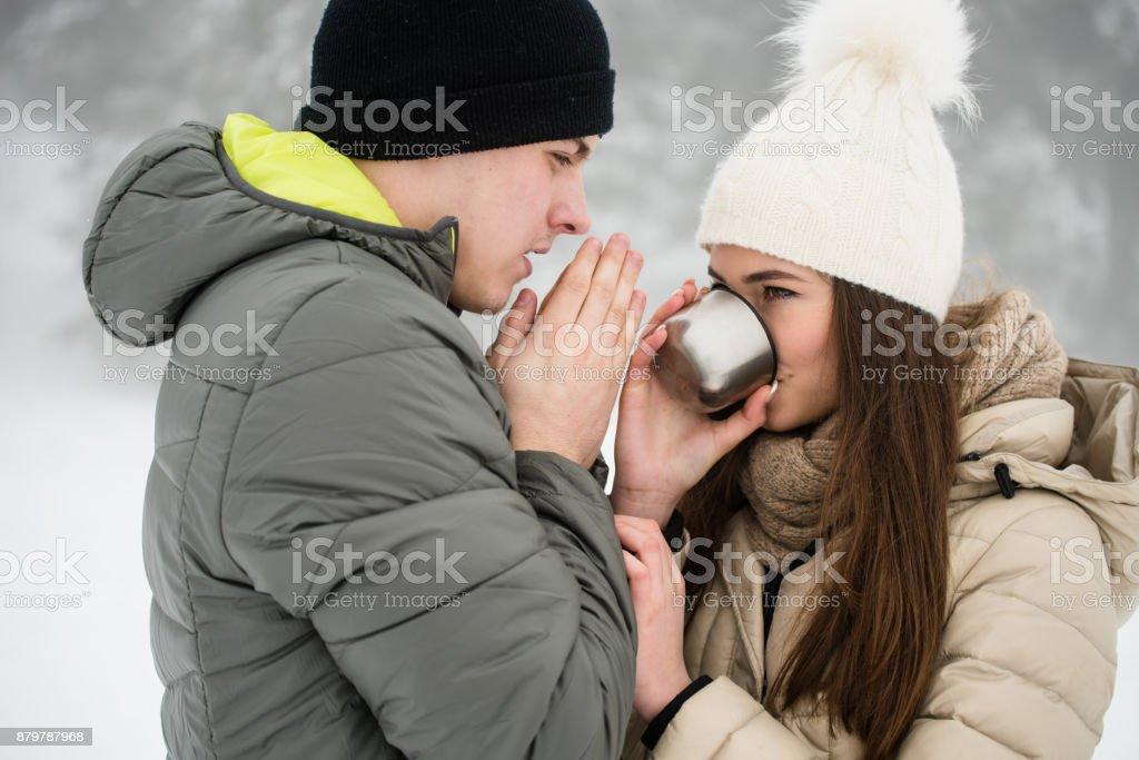 Couple outdoors in winter drinking tea stock photo