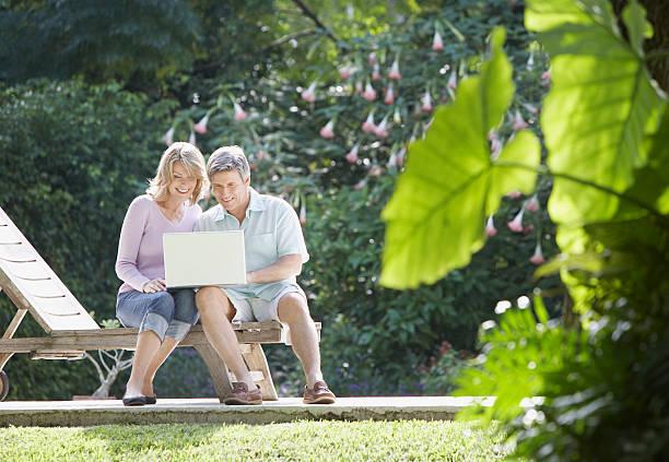 paar mit laptop im freien im hof - garden types stock-fotos und bilder