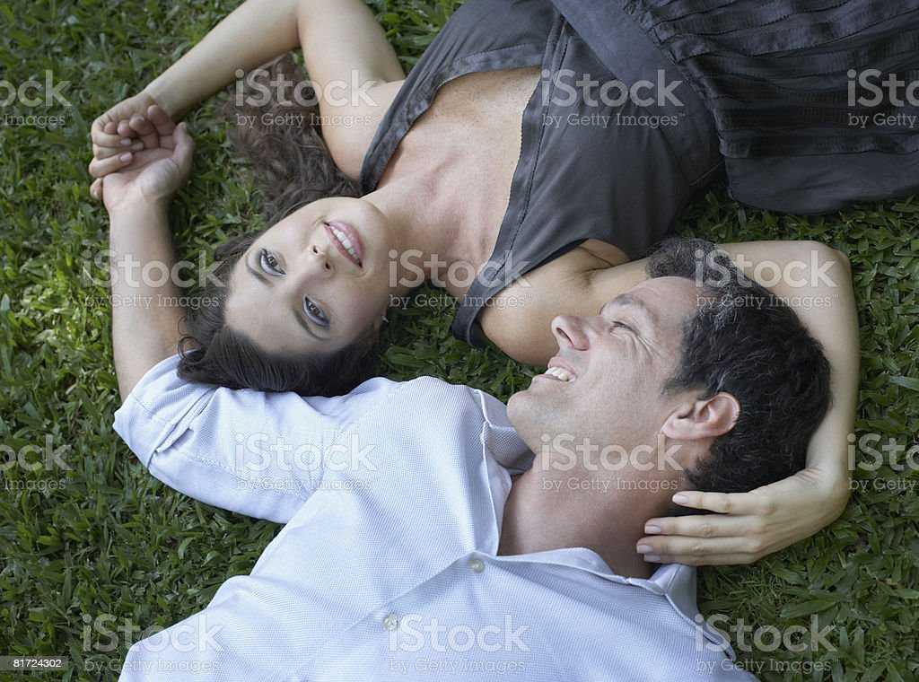Couple outdoors lying on grass together holding hands and smiling stock photo