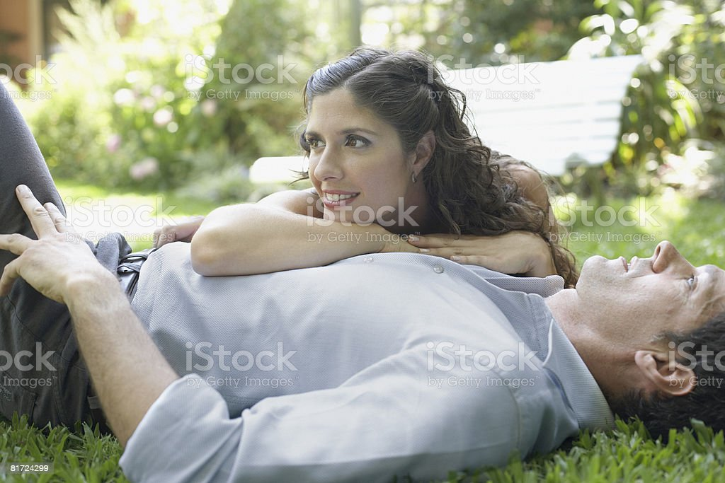 Couple outdoors lying on grass together smiling royalty-free stock photo
