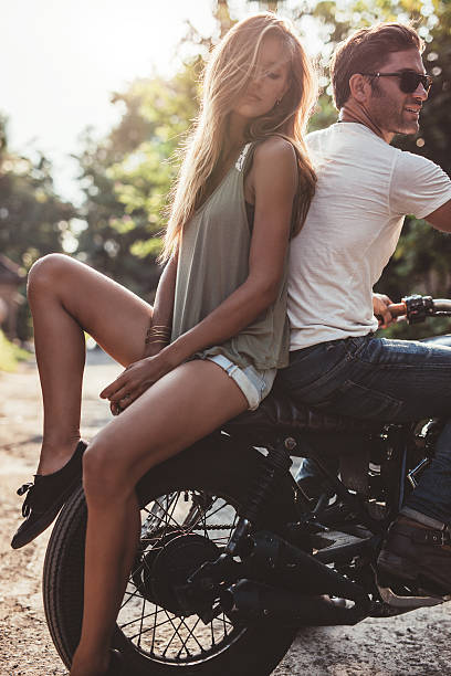 couple outdoors on motorbike - country fashion stock photos and pictures