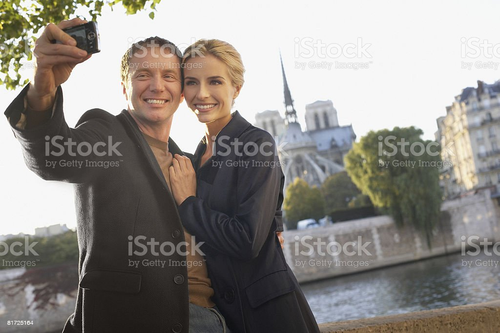 Couple outdoors taking self-portrait using digital camera smiling stock photo
