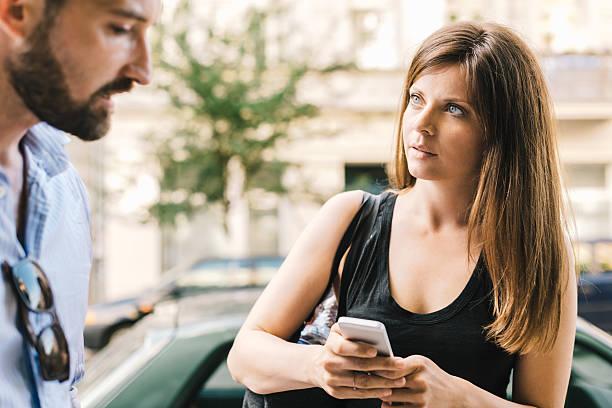 couple outside on street, woman with mobile phone - kvinna cloes up bildbanksfoton och bilder