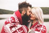 Couple kissing outside under the blanket