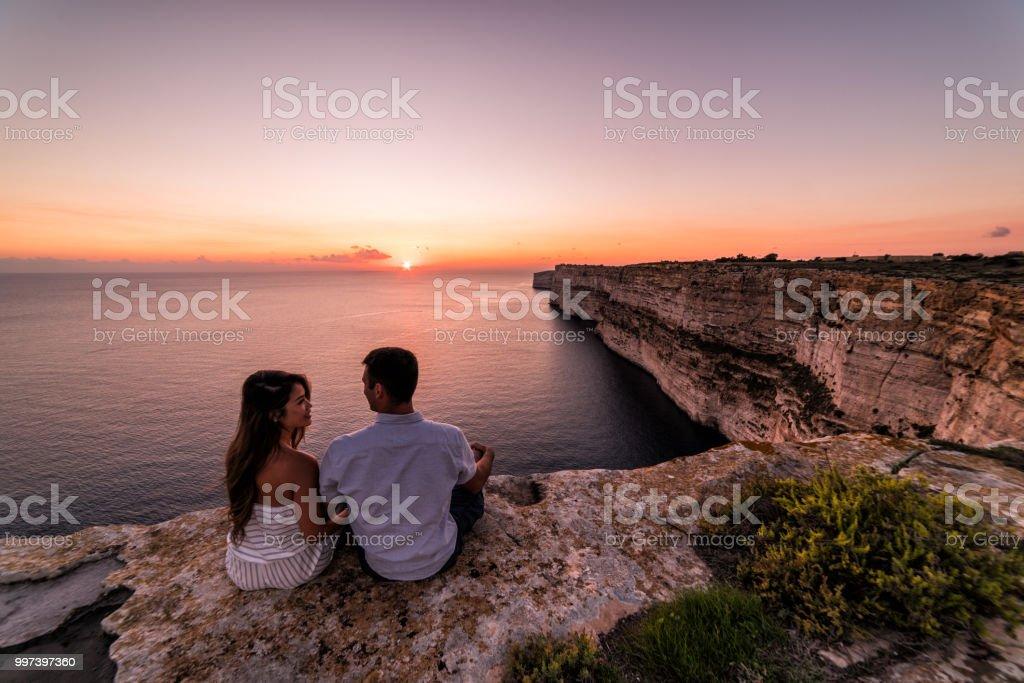 Couple overlooks the Ta Cenc cliffs at sunset.  Gozo, Malta stock photo