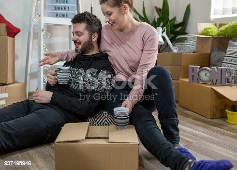 Couple packing stuff among plenty of cardboard boxes