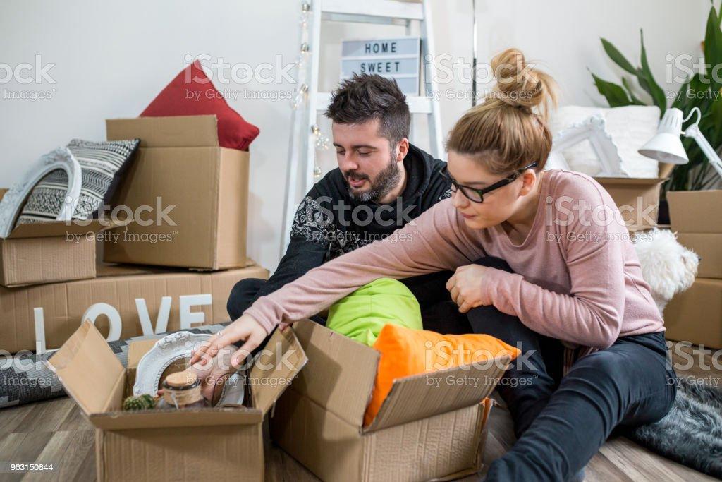 Par packning grejer bland massor av kartonger - Royaltyfri Avkoppling Bildbanksbilder