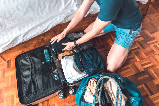 Couple packing suitcase for vacation at home stock photo