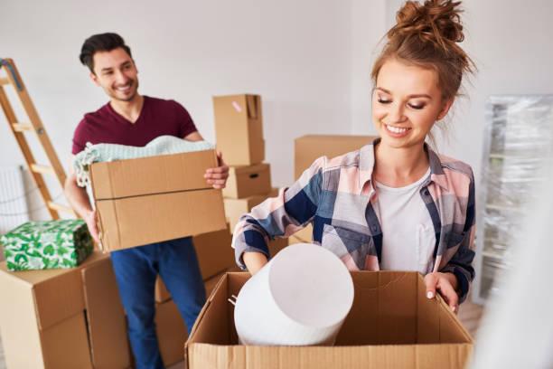 Pareja empacando sus cosas en cajas durante la casa de mudanzas - foto de stock