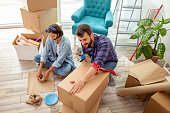 istock Couple packing things into cardboard boxes 1207283284