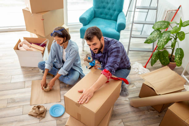 Couple packing things into cardboard boxes stock photo