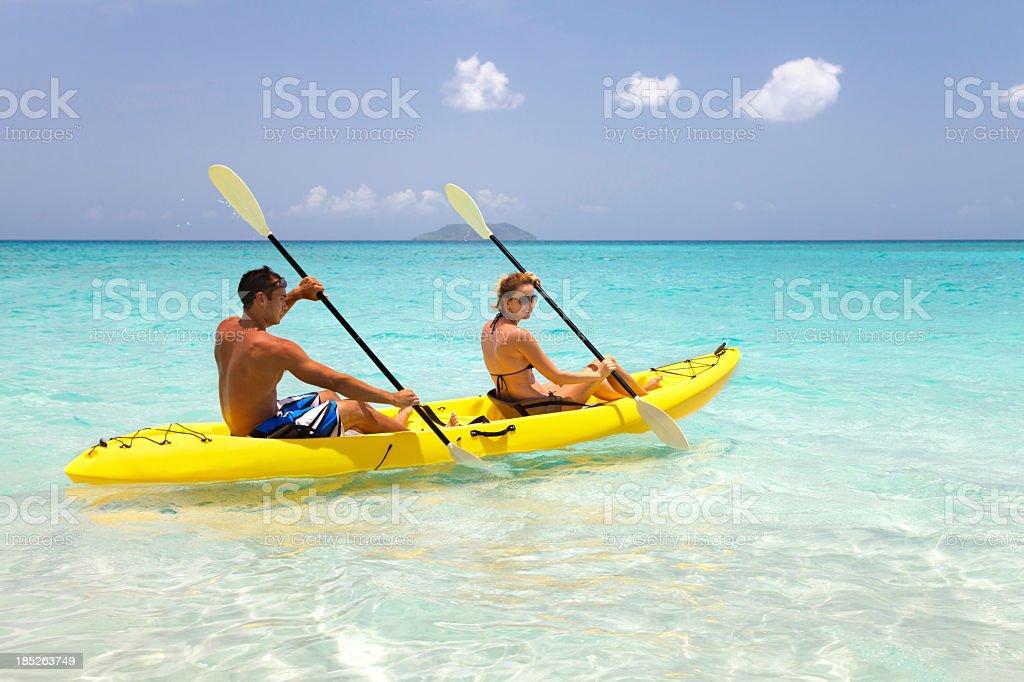 couple paddling in yellow kayak through the Caribbean water stock photo