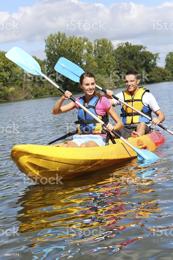 Couple paddling together on river stock photo