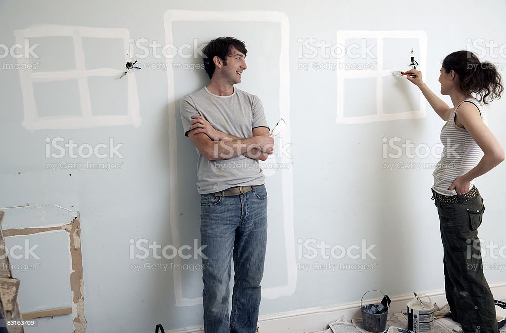Couple painting doors and windows on an old wall royalty free stockfoto