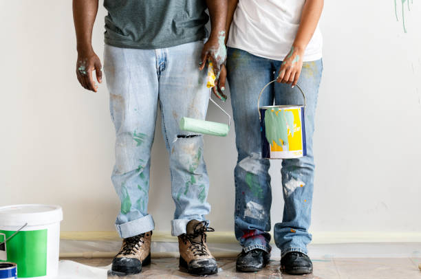 Couple painting house wall stock photo