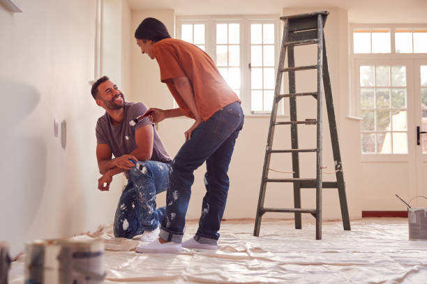 Couple Painting Test Squares On Wall As They Decorate Room In New Home Together stock photo