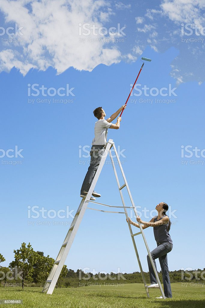 Couple painting the sky blue royaltyfri bildbanksbilder