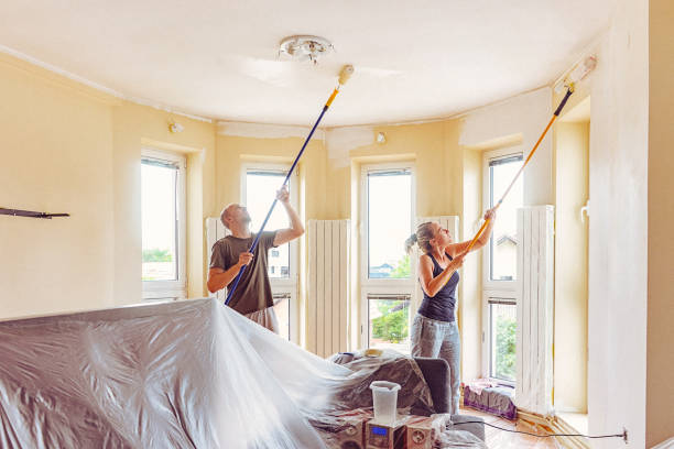 Couple painting wall and ceiling with telescopic roller stock photo