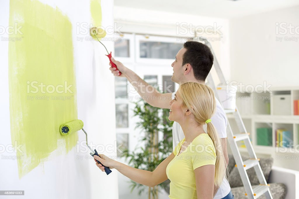 Couple painting wall at home Affectionate couple painting together a room in their new house Adult Stock Photo