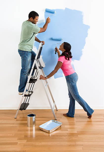 Couple painting wall blue. stock photo