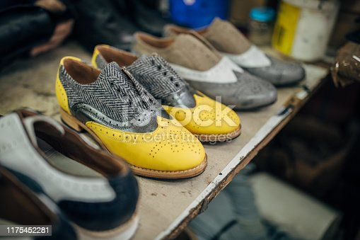 Couple pair of shoes on shelf in shoe factory, no people.