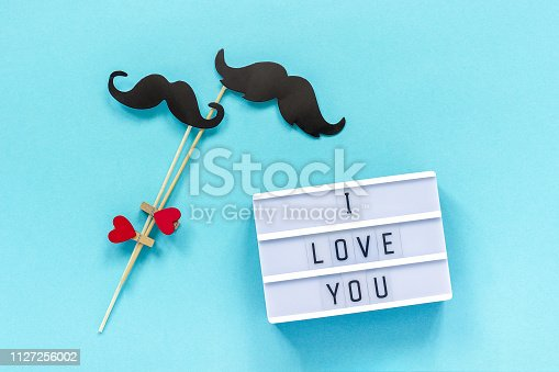 Couple paper mustache props and Light box with text I love you on blue background. Concept Homosexuality gay love National Day Against Homophobia or International Gay Day Top view Greeting card