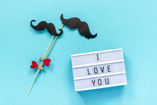 Couple paper mustache props and light box with text I love you on blue background. Concept Homosexuality gay love. National Day Against Homophobia or International Gay Day Top view Greeting card stock photo