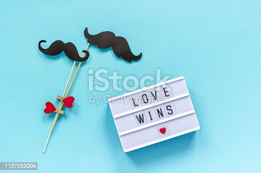Couple paper mustache props and Light box with text Love wins on blue background. Concept Homosexuality gay love National Day Against Homophobia or International Gay Day Top view Greeting card