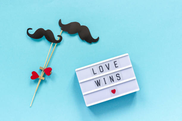 Couple paper mustache props and light box with text Love wins on blue background. Concept Homosexuality gay love. National Day Against Homophobia or International Gay Day Top view Greeting card stock photo