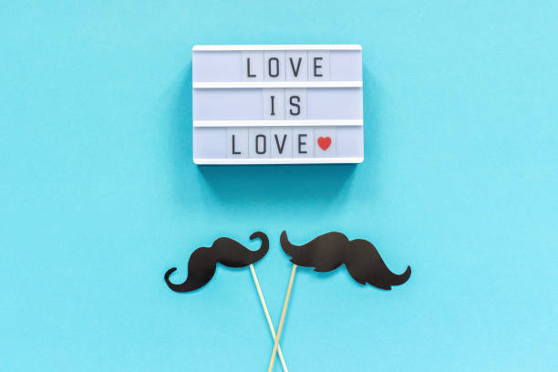 Couple paper mustache props on stick and light box with text Love is love on blue background. Concept Homosexuality gay love. International Gay Day or Valentine's Day Top view Greeting card Template stock photo