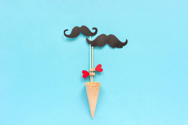 Couple paper mustache props on stick fastened clothespin heart in ice cream waffle cone on blue background. Concept Homosexuality gay love. International Gay Day or Valentine's Day Greeting card stock photo