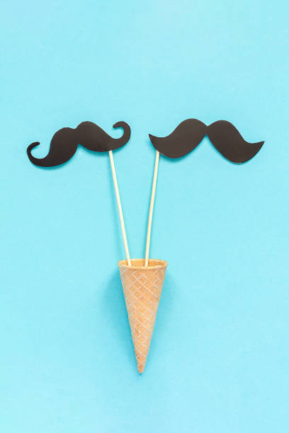 Couple paper mustache props on stick in ice cream waffle cone on blue background. Concept Homosexuality gay love. International Gay Day or Valentine's Day Greeting card Top-down composition stock photo
