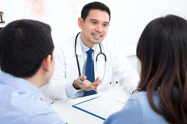 Couple patients consulting with Asian male medical doctor in hospital room stock photo