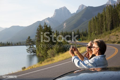 527894422 istock photo Couple pause beside car, taking picture on mountain road 1071099070
