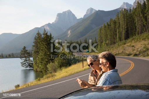 527894422 istock photo Couple pause beside car, taking picture on mountain road 1071099078