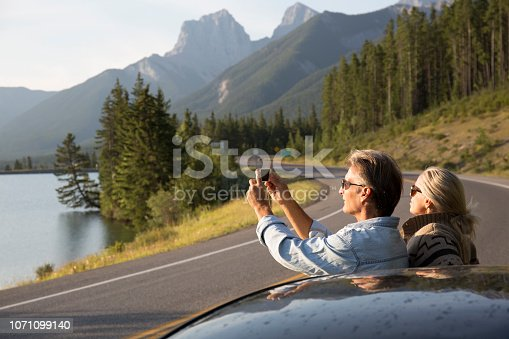 527894422 istock photo Couple pause beside car, taking picture on mountain road 1071099140
