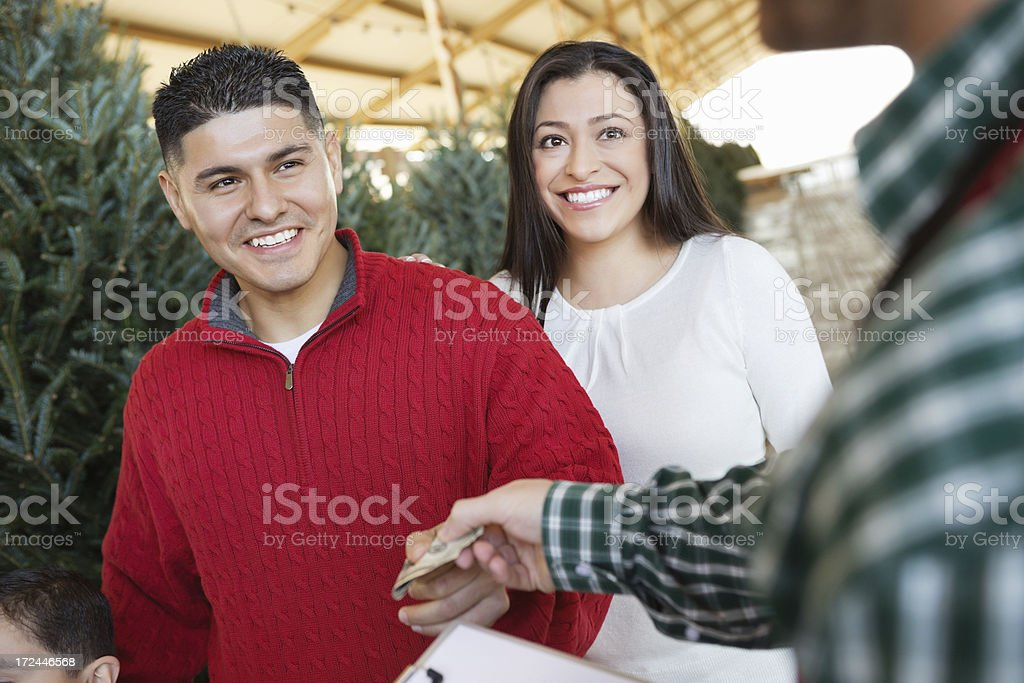Couple paying cashier after choosing perfect Christmas tree royalty-free stock photo