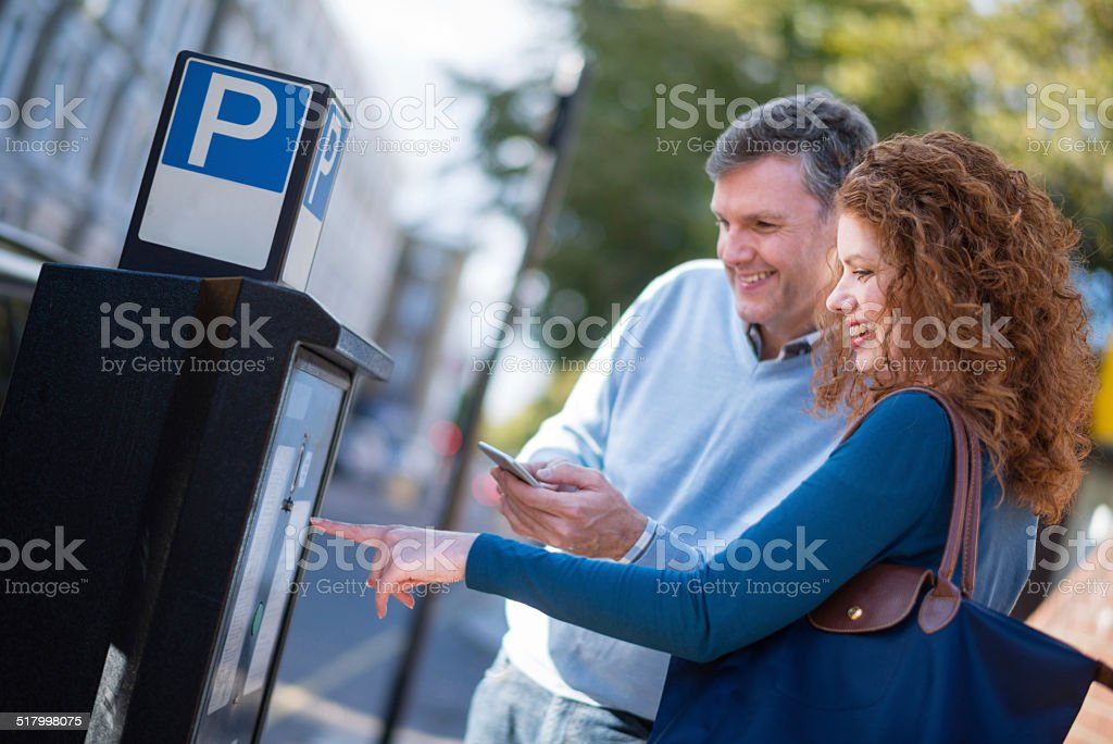 Couple paying for parking stock photo