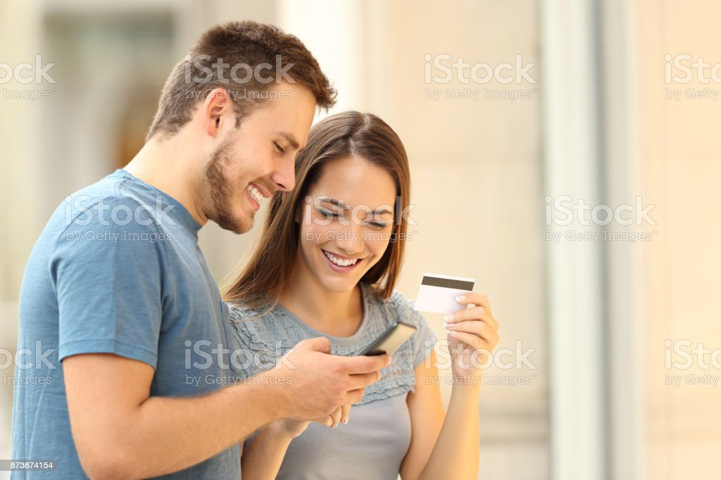 Couple paying on line with credirt card on the street - foto stock