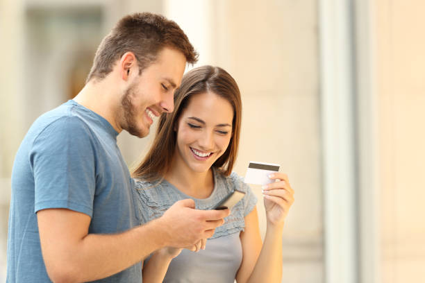 couple paying on line with credirt card on the street - online shopping imagens e fotografias de stock