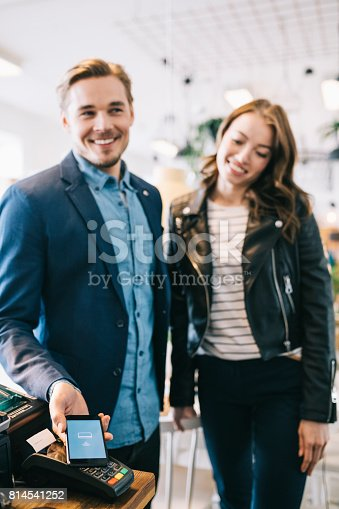 istock Couple paying with smartphone. 814541252