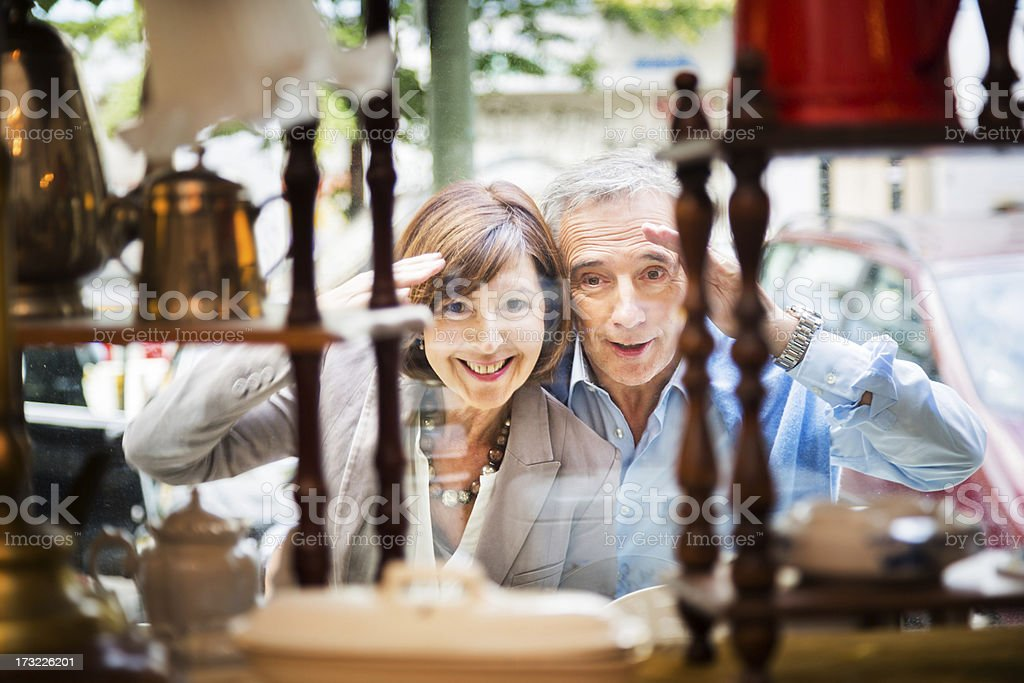 Couple Peeking Through Shopping Window stock photo